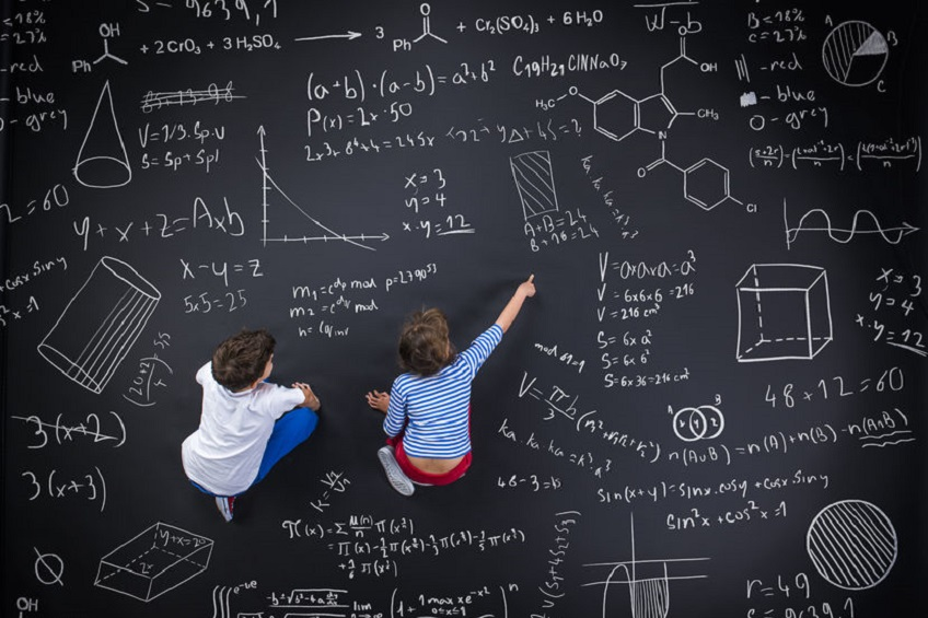 35548261 - cute boy and girl learning playfully in frot of a big blackboard